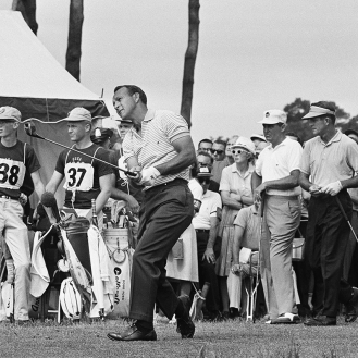 Arnold Palmer Ligonier, Pa., winner of the U.S. Open golf championship in 1960, watches flight of his tee shot on first hole at The Country Club, June 20, 1963 in Brookline, Mass., at start of the 1963 USGA Open. Playing in threesome with Palmer are Jay Hebert, right, of Lafayette, La., and Doug Ford of Brookville, N.Y. (AP Photo)