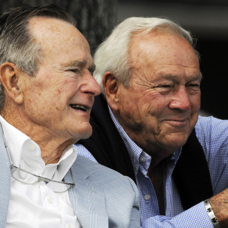 Former President George H. W. Bush, left, and legendary golfer Arnold Palmer talk as they ride around the golf course at the Champions Tour golf in 2010. (AP Photo/Pat Sullivan)