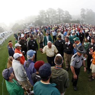 Honorary starter Arnold Palmer walks through the crowd after teeing off to start the first round of the 2008 Masters. (AP Photo/Rob Carr)