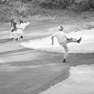 Both Arnold Palmer and his caddy throw themselves in to the act as Palmer's Eagle putt rolls close to the 13th cup but misses by inches in the final round of the 1963 Masters Tournament. (AP Photo)