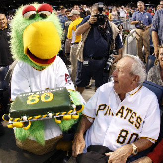 Arnold Palmer is surprised by the Pirate Parrot and a birthday cake in his seat behind home plate during the Pittsburgh Pirates and Chicago Cubs game in 2009.
