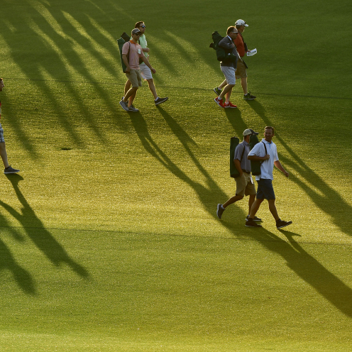 The shadows of Masters patrons precede them on the No. 1 hole during the first round of the Masters. (Augusta National)
